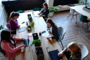 Women work at long table with their laptops
