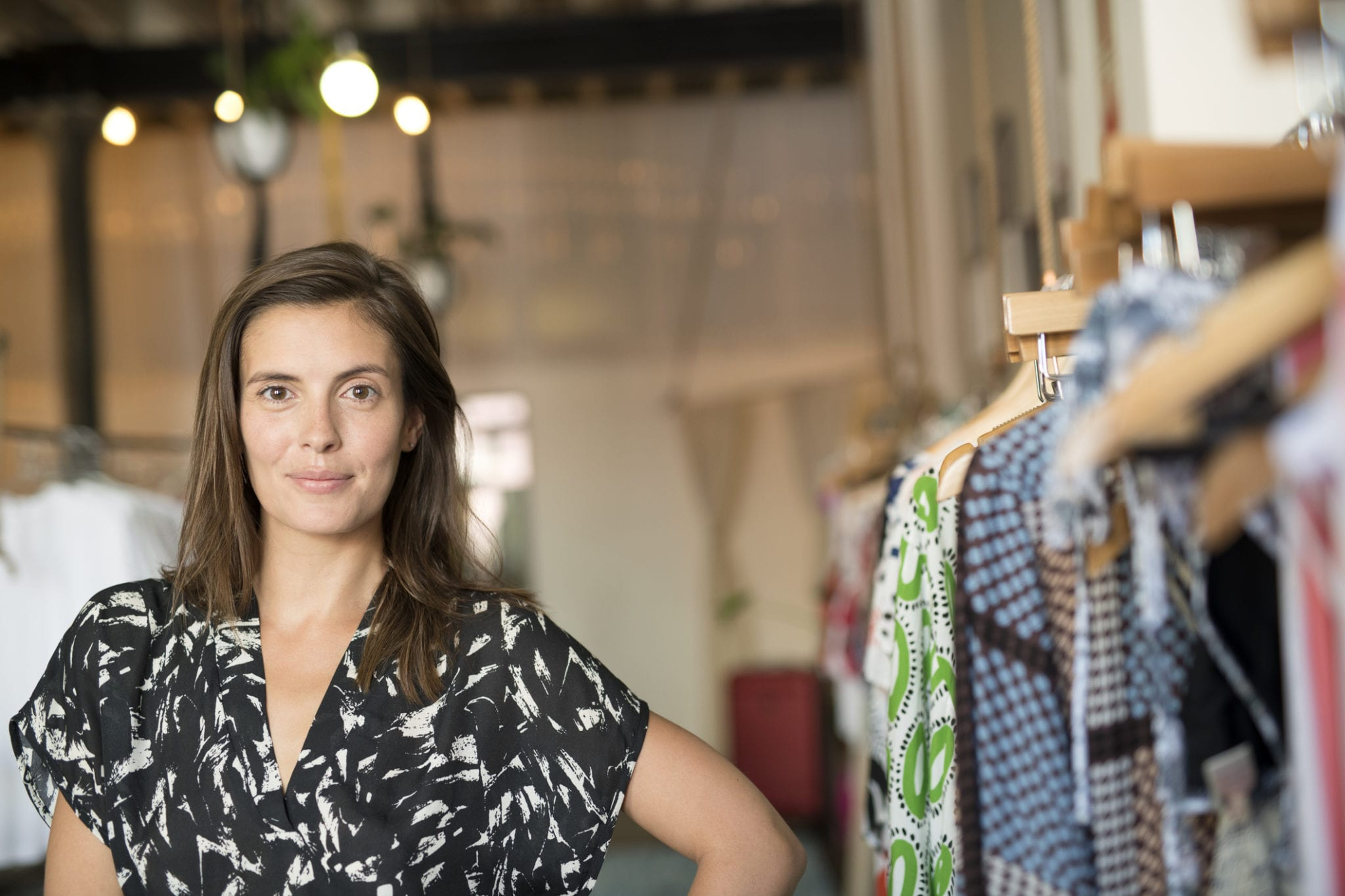 Woman fashion business designer beside clothes rack in store